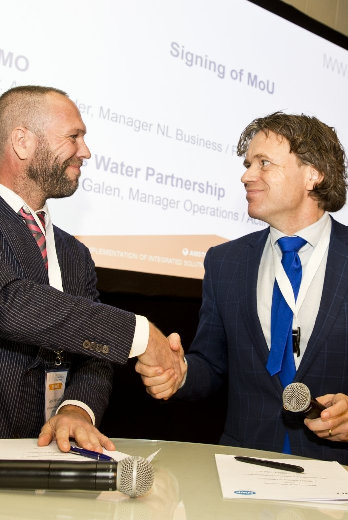 NWP acting director Ewout van Galen and Aart Mulder of FMO Development Bank shake hands on the renewal of the MoU at the AIWW Summit 2018