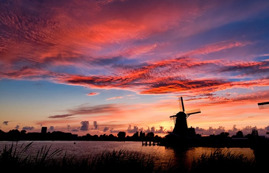 Photo of a Dutch landscape with a couple of windmills next to a canal.